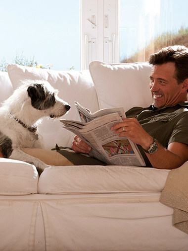 Dog laying on sofa with owner as he reads newspaper